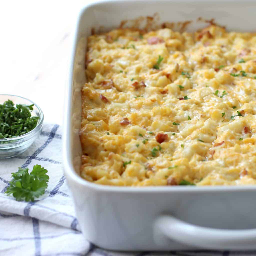 Cheesy Bacon Potato Casserole with garnishes on the side