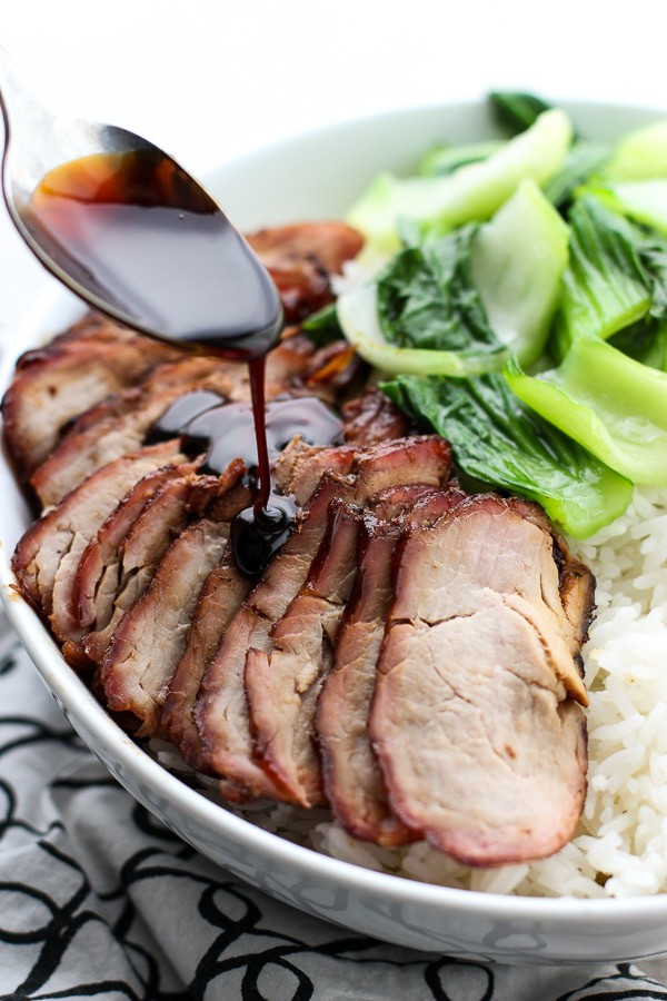 Drizzling sauce onto Chinese Barbecue Pork (char Siu) and Bok Choy Rice Bowl