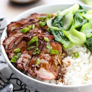Chinese Barbecue Pork (char Siu) and Bok Choy Rice Bowl with a small bowl of sauce in the background