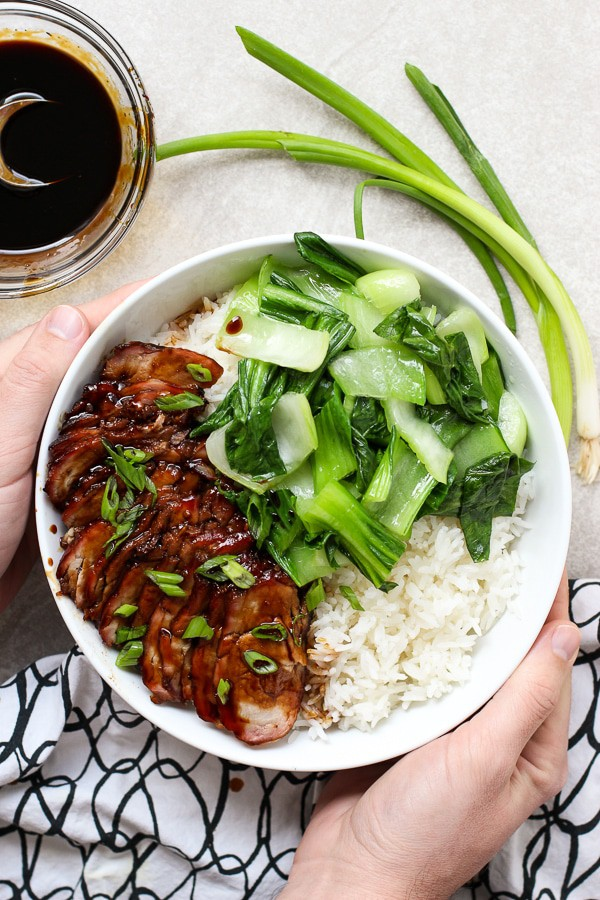 Hands holding Chinese Barbecue Pork (char Siu) and Bok Choy Rice Bowl