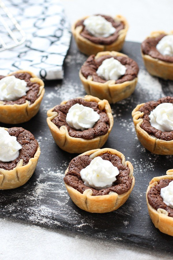 A tray of Mini Chocolate Chess Pie with whipped cream on top