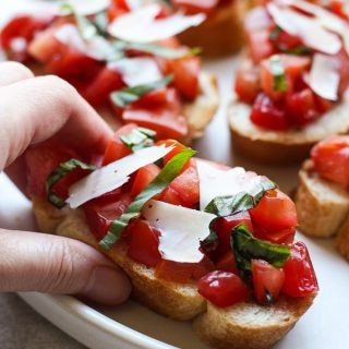 Hand grabbing a piece of Bruschetta with Tomatoes, Basil and Balsamic Vinegar