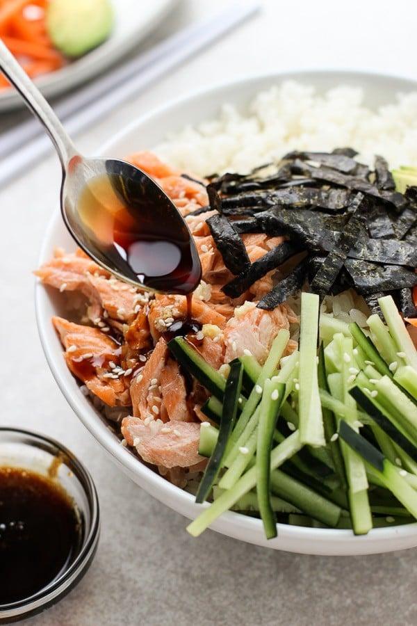 Adding sauce to Baked Salmon Sushi Bowl