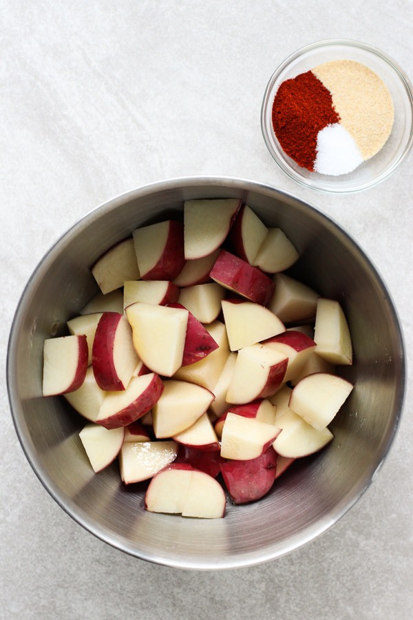 A bowl of uncooked diced red potatoes with a small bowl of spices for Roasted Garlic Parmesan Potatoes
