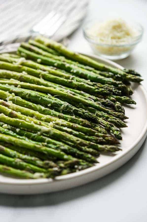 A plate of Easy Garlic Parmesan Asparagus with a small bowl of parmesan cheese in the background