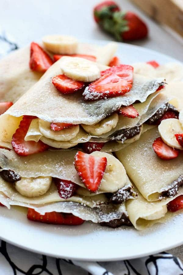 Strawberry Banana Nutella Crepes stacked on a plate