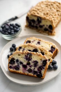 Three slices of blueberry bread with crumb topping on a plate with the loaf in the background