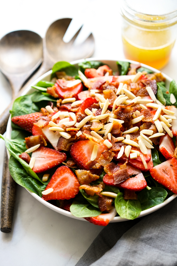 A bowl of Strawberry Bacon Spinach Salad with Lemon Maple Dressing on the side