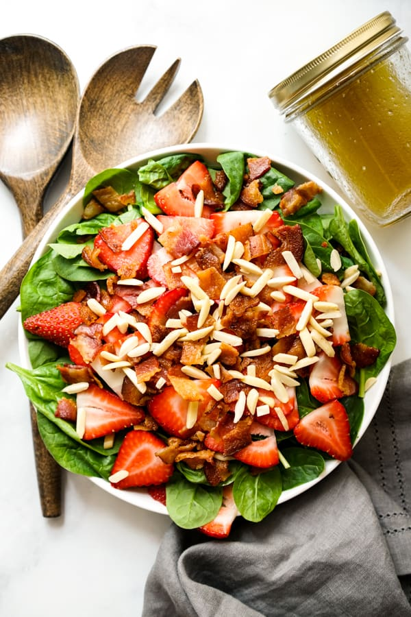 Top down look of Spinach Salad topped with bacon and strawberries and almonds, with Lemon Maple Dressing