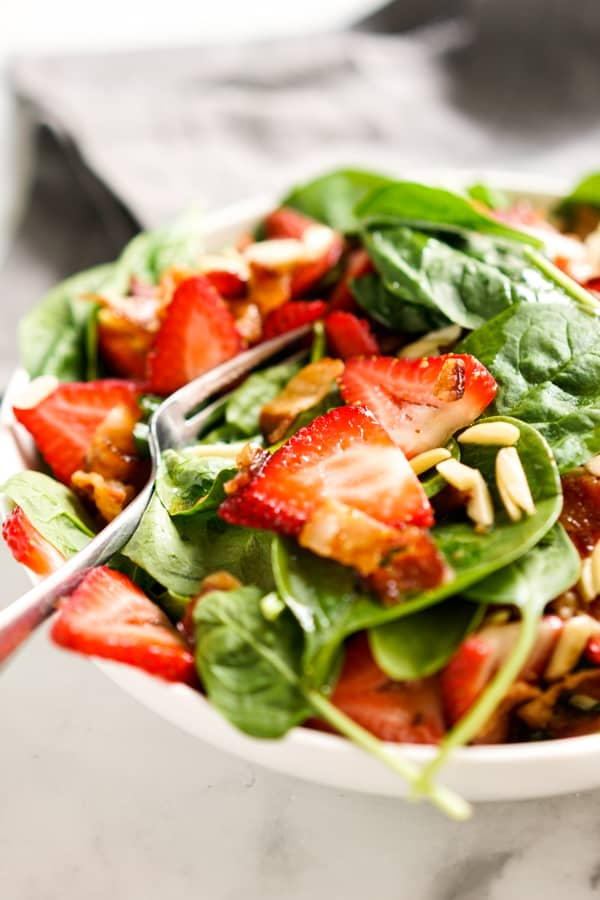 Fork digging into strawberry spinach salad