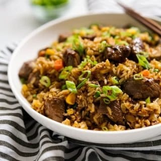 A bowl of fried rice with steaks with a pair of chopsticks on the bowl