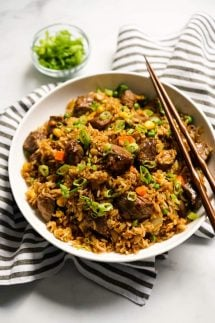 A bowl of Steak Fried Rice with kitchen towel tucked underneath and a pair of chopsticks on it