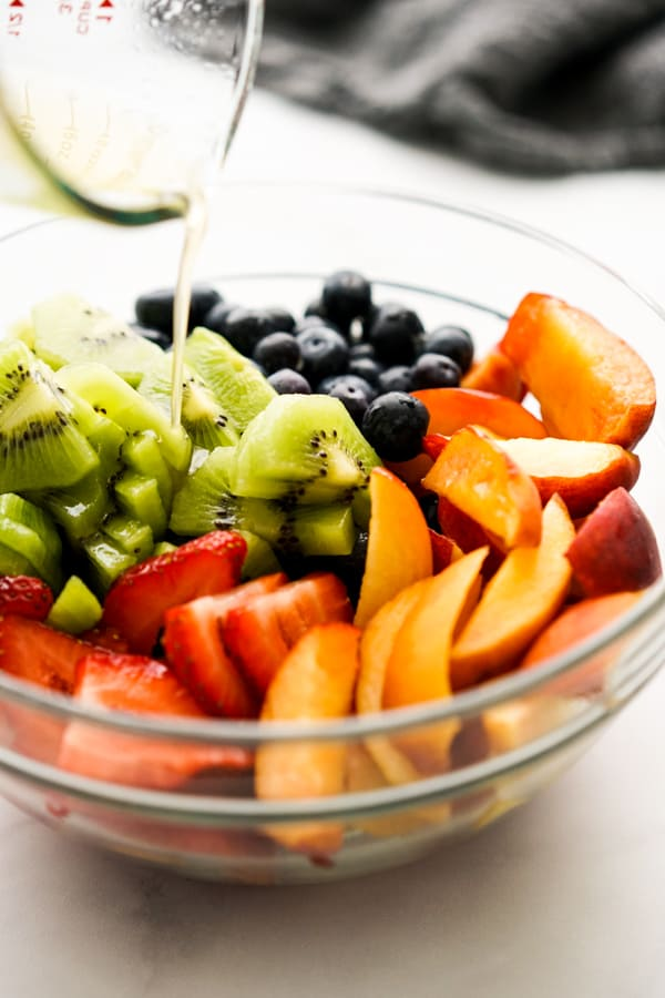 Pouring Honey Lime Dressing onto a bowl of fruit salad