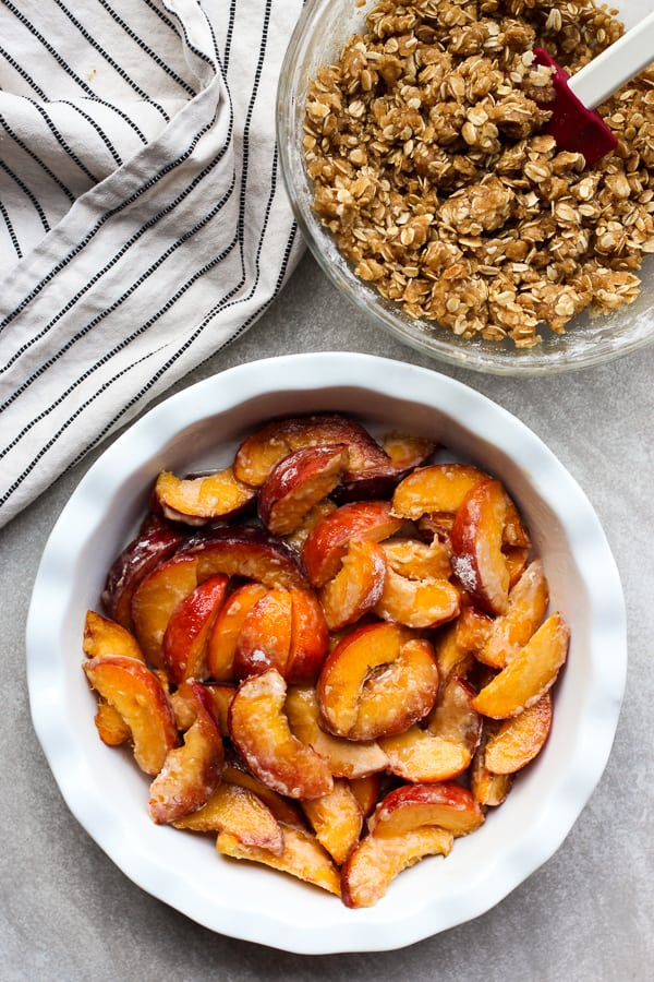 Fresh peaches in a round pan with a bowl of crumble on the side