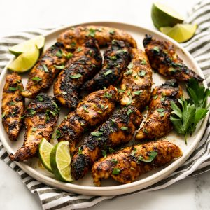 A plate of grilled cajun chicken garnish with parsley and lime