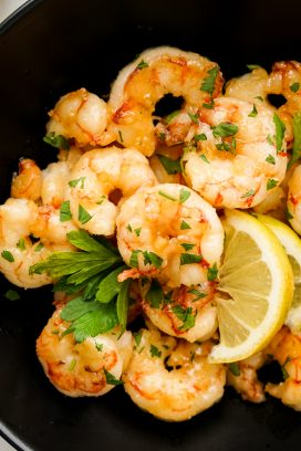 A plate of shrimp with lemon wedges