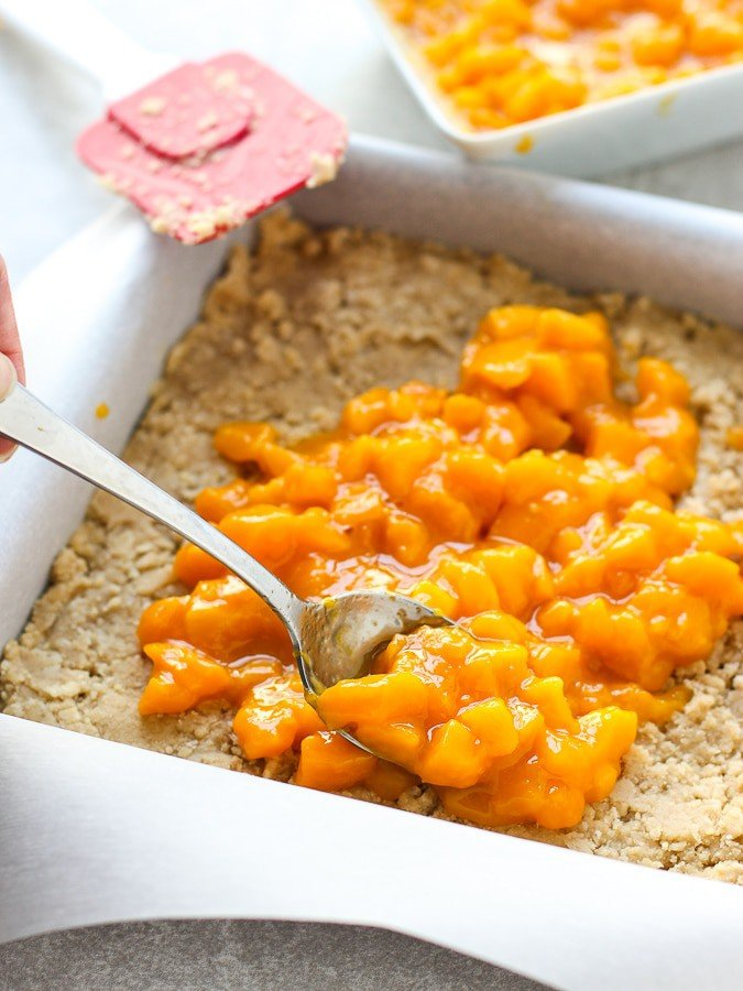 Spreading mango filling onto crumble