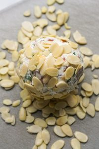 Coating cheeseball with shaved almonds