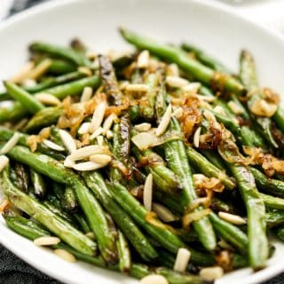 A plate of charred green beans topped with Caramelized Onions