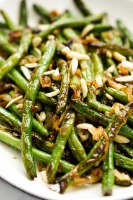 A plate of green beans topped with caramelized onions