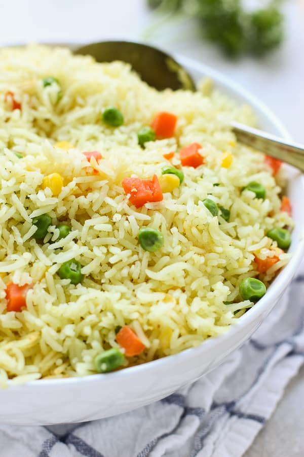 A big bowl of Easy Mixed Vegetable Rice with a spoon in it