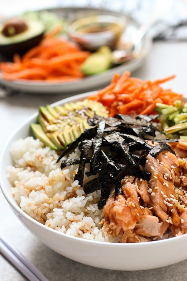 A bowl of Baked Salmon Sushi Bowl with garnishes in the background