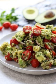 A plate of Avocado Quinoa Salad with avocados and tomatoes in the background