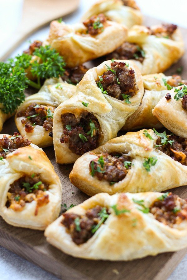 Many Sausage and Cheese Puff Pastry Pockets on a cutting board