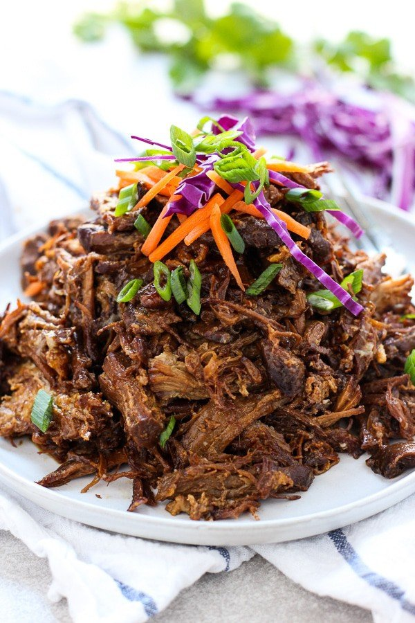 Slow Cooker Asian Shredded Pork with garnishes on a plate