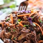 Slow Cooker Asian Shredded Pork on a plate, with a fork digging into it