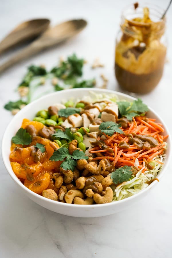 A bowl of Asian salad with shredded cabbage, carrots and cashews with peanut dressing in the background