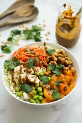 Asian Peanut Chicken Salad ingredients in a large bowl with peanut dressing and spatulas in the background