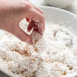 Coating chicken in flour mixture to make Sweet and Sour Chicken