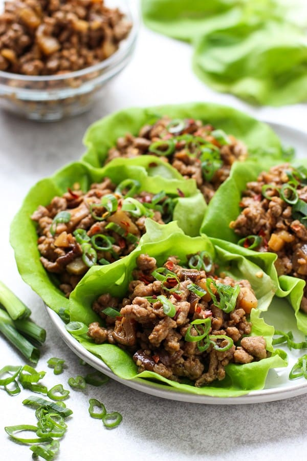 A plate of Asian Lettuce Wraps with a bowl of ground pork and lettuce in the background
