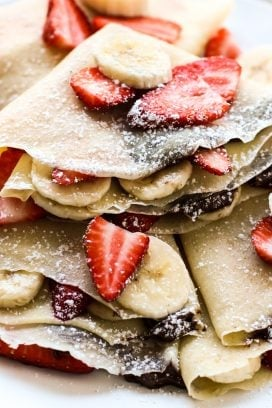 A plate of strawberry banana nutella crepes