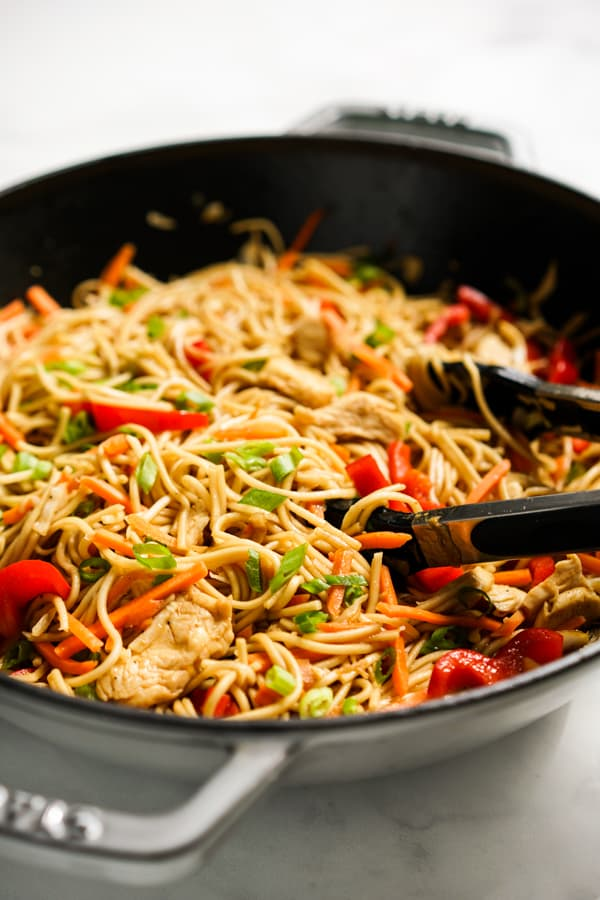 Lo Mein noodles with bell peppers, chicken and carrots in a large frying pan