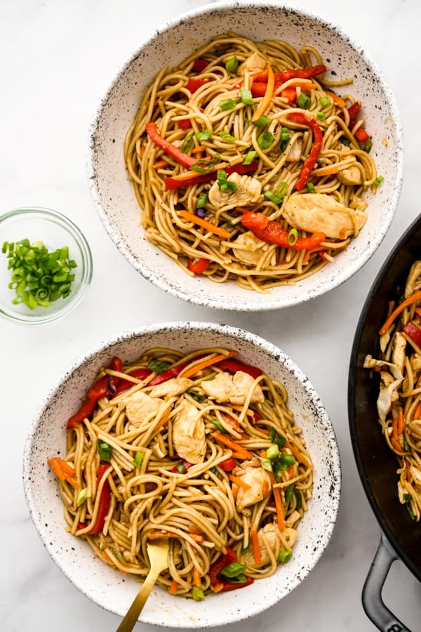 A bowl of Chicken Lo Mein with chopsticks in the background