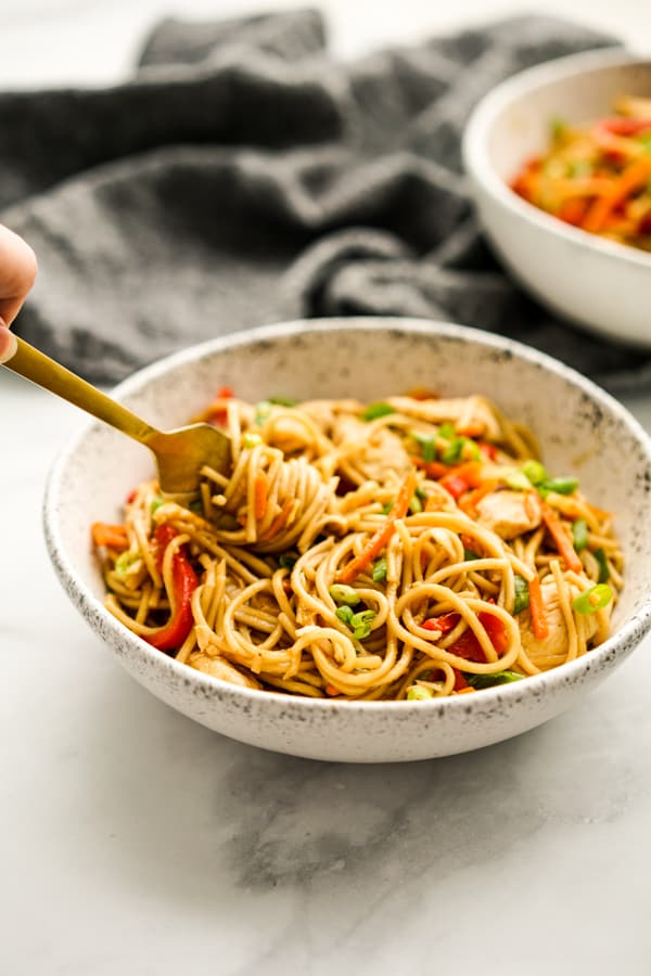 Chicken Lo Mein on a bowl with chopsticks picking the noodles