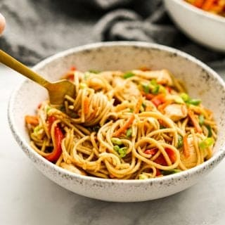 Using a fork to dig into a bowl of Chicken Lo Mein