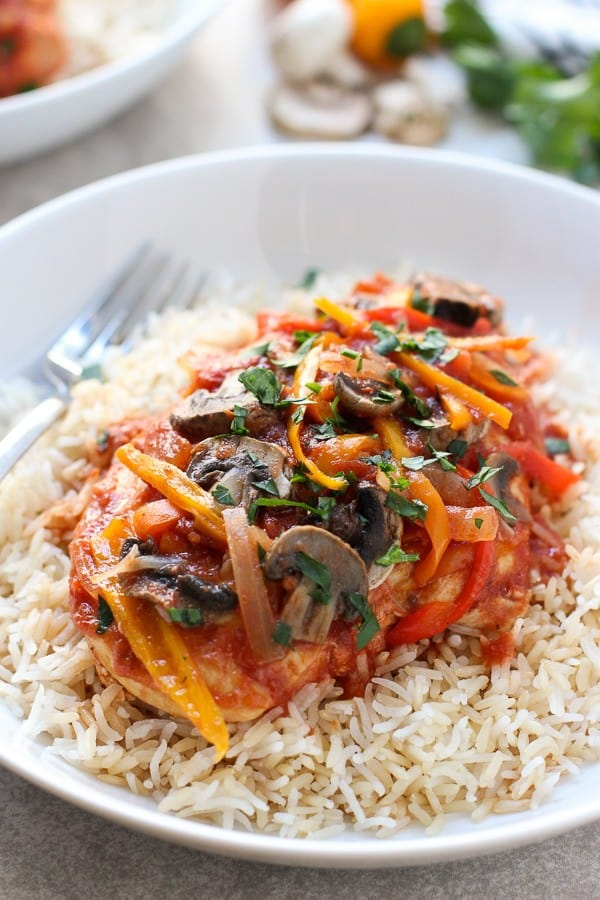 Slow Cooker Tomato and Herb Chicken with rice on a plate with a fork on the background