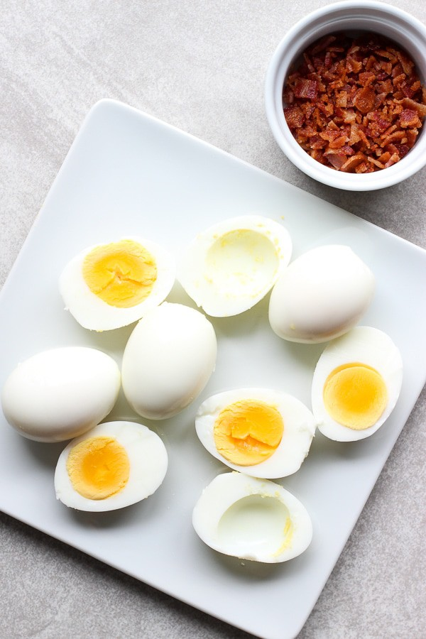 Top down shot of a plate of boiled eggs with bacon bits in the background for Bacon Deviled Eggs