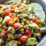 A bowl of Avocado Corn and Black Bean Salsa with lime wedges on the side