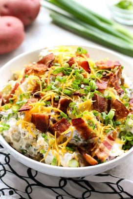 Loaded Baked Potato Salad with green onions and red potatoes behind it