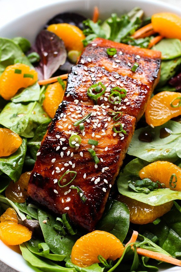 A bowl of Asian Salmon Salad with lettuce, mandarin oranges and green onions