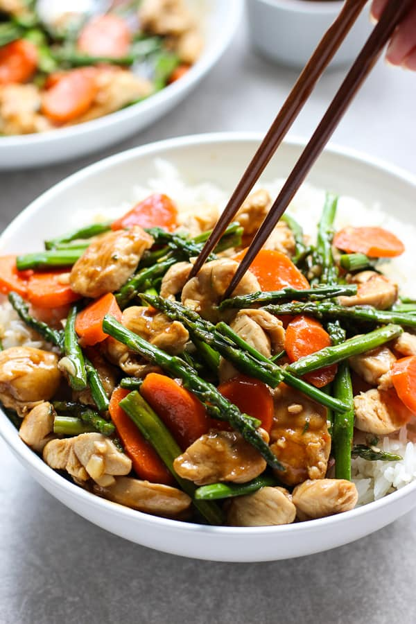 A pair of chopsticks digging into chicken and asparagus stir fry