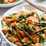 A bowl of Chicken and Asparagus Stir Fry on top of a bed of rice