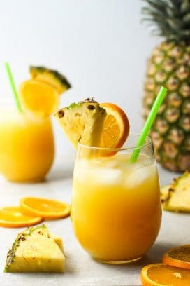 Two glasses of orange and pineapple coconut rum cocktails, with a pineapple in the background