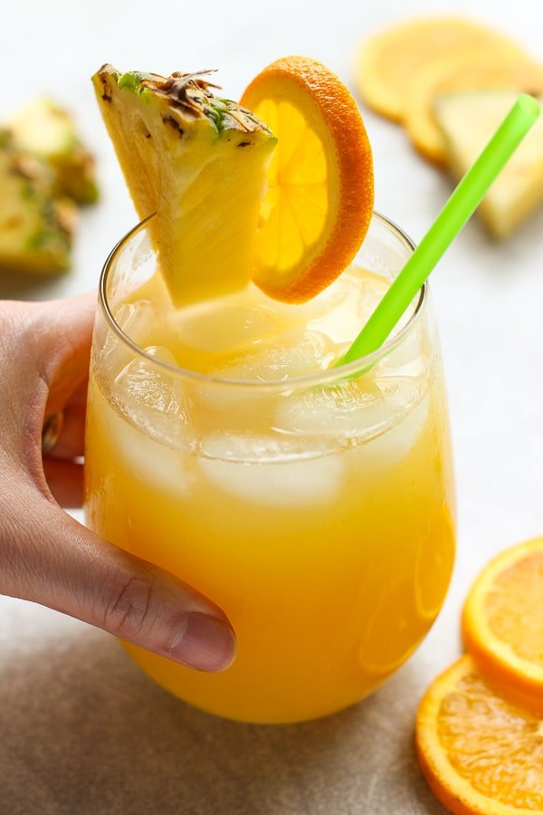 Hand holding on to a glass of Orange and Pineapple Coconut Rum Cocktail