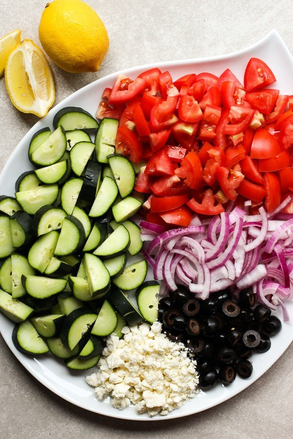 A large plate filled with tomatoes, cucumber, onions, olives and feta cheese