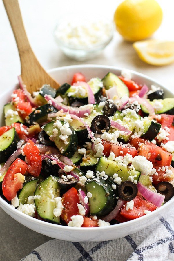 A large bowl of cucumber, tomatoes, red onions and olives tossed in Greek Lemon dressing. Serving spoon in the bowl.
